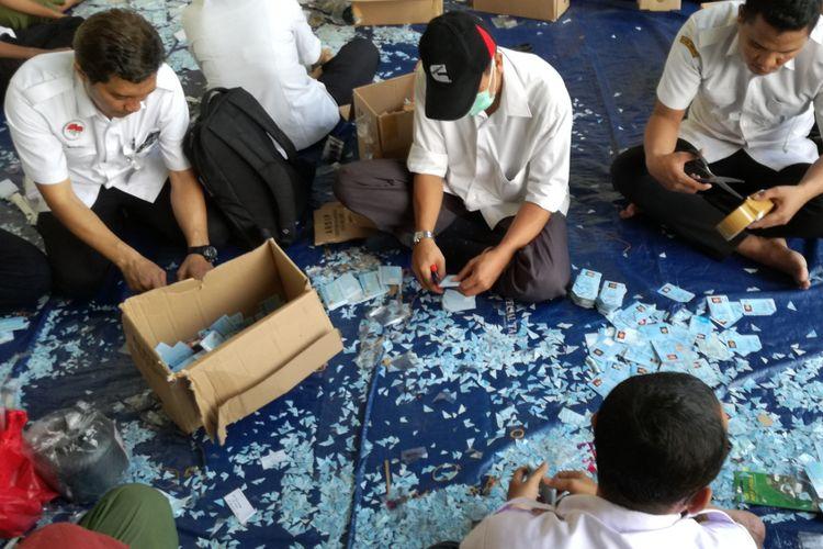 Sejumlah staf dukcapil Kemendagri memotong ujung kanan atas e-KTP yang rusak di gudang penyimpanan barang inventarisasi Kemendagri, Bogor, Jawa Barat, Rabu (30/5/2018).