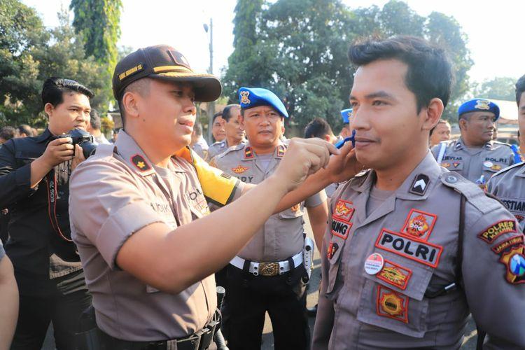 Wakapolres Kediri Kompol Andik Gunawan saat membersihkan bulu di wajah anggotanya pada apel pagi, Senin (14/10/2019).