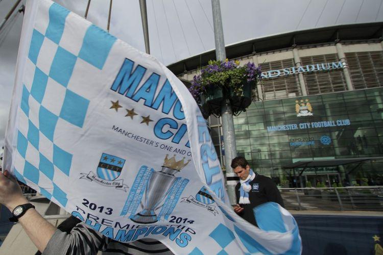 Seorang fans Manchester City membentangkan bendera juara Premier League dan Piala Liga Inggris saat Man City memastikan gelar juara Liga Inggris 2013-2014 di Stadion Etihad, Manchester, pada 11 Mei 2014.
