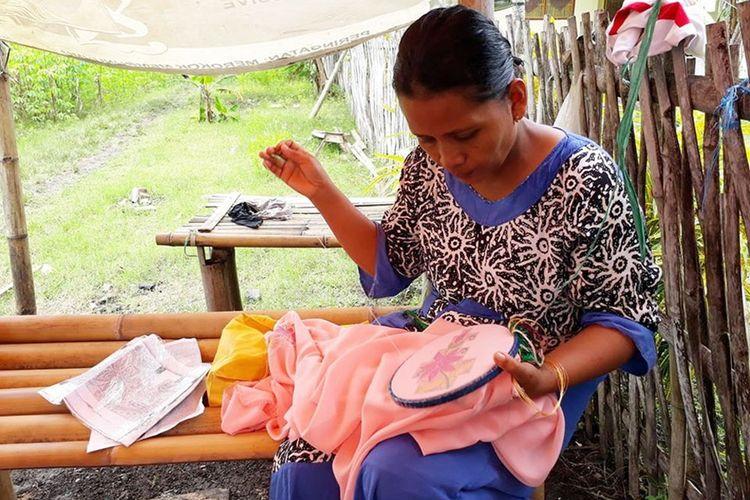 Seorang wanita di desa menyulam selembar kain di sela kegiatan rumah tangganya. Berbekal kertas bergambar motif, jarum, dan midangan, proses sulam karawo dilakukan pada selembar kain.