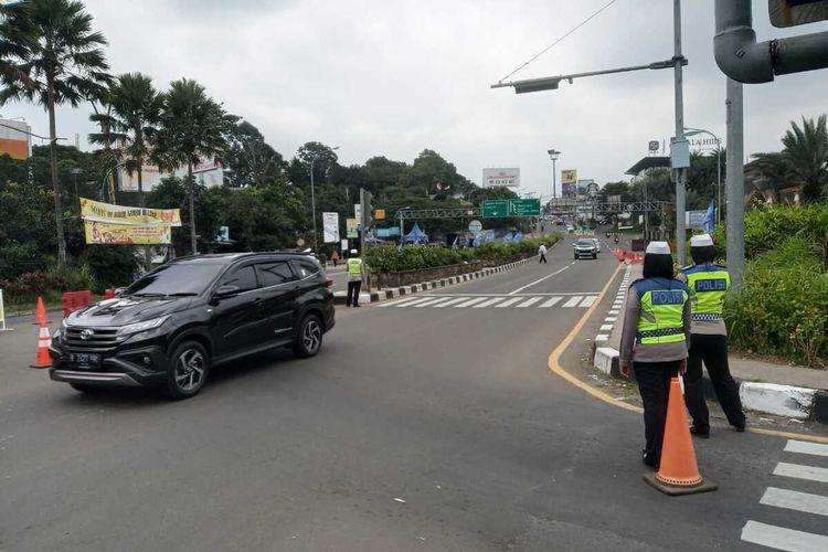 Petugas kepolisian tengah mengatur Rekayasa lalu lintas sistem one way atau satu arah turun ke bawah atau Jakarta di Simpang Gadog, Ciawi, Kabupaten Bogor, Jawa Barat, Minggu (26/9/2021).