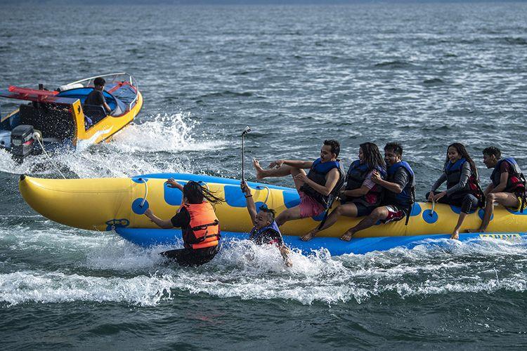 Foto dirilis Jumat (5/3/2021), memperlihatkan wisatawan menikmati permainan banana boat di perairan Danau Toba di kawasan Tuktuk Siadong, Samosir, Sumatera Utara. Pemerintah Indonesia saat ini tengah menyiapkan Danau Toba di Sumatera Utara sebagai lokasi Destinasi Pariwisata Super Prioritas (DPSP) untuk menggantikan Pulau Bali.
