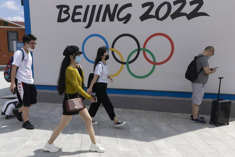 Pengunjung Chongli, salah satu tempat Olimpiade Musim Dingin Beijing 2022, melewati logo Olimpiade di Chongli di Provinsi Hebei, China utara pada 13 Agustus 2020.