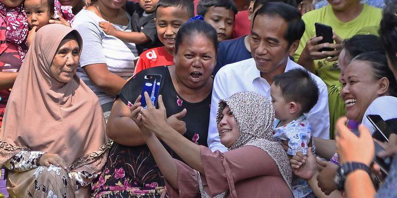 Capres petahana Joko Widodo menyapa warga sebelum menyampaikan pidato kemenangannya sebagai Presiden Republik Indonesia periode 2019-2024 di Kampung Deret, Tanah Tinggi, Johar Baru, Jakarta Pusat, Selasa (21/5/2019). Pidato tersebut menanggapi keputusan Komisi Pemilihan Umum (KPU) yang menetapkan pasangan Joko Widodo-Maruf Amin sebagai pemenang Pilpres 2019.