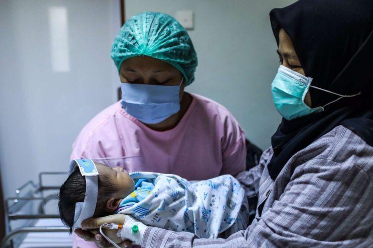 bSeorang ibu menggendong bayinya yang memakai pelindung wajah di Rumah Sakit Ibu dan Anak (RSIA) Tambak, Jakarta Pusat, Rabu (23/5/2020). Rumah Sakit Ibu dan Anak (RSIA) menerapkan kebijakan baru berupa pemakaian face shield atau pelindung wajah untuk bayi yang sedang mendapat perawatan maupun yang baru dilahirkan di RS tersebut. Hal tersebut dilakukan untuk mencegah terjadinya penularan virus corona jenis baru atau SARS-CoV-2 yang menyebabkan penyakit Covid-19.