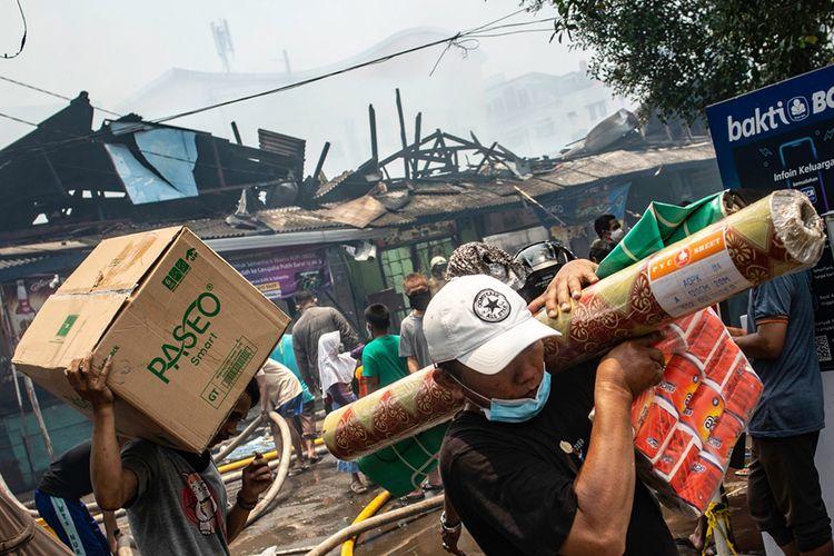 Pedagang mengevakuasi barang dagangannya saat terjadi kebakaran di Pasar Cempaka Putih, Jakarta, Kamis (24/9/2020). Kurang lebih 20 unit mobil pemadam kebakaran dikerahkan untuk memadamkan api, sedangkan penyebab kebakaran masih dalam penyelidikan pihak yang berwenang.