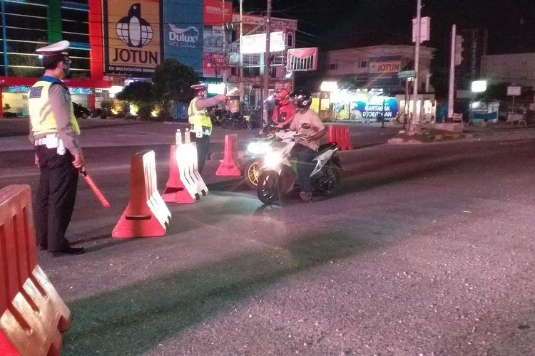 Petugas Satlantas Polresta Pekanbaru menyetop kendaraan yang melintasi Jalan HR Soebrantas dan dialihkan ke jalan lain dalam masa PSBB untuk mencegah penyebaran Covid-19 di Kota Pekanbaru, Riau, Jumat (24/4/2020) malam.