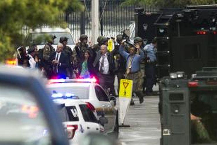 Sejumlah orang terlihat mengangkat tangan sembari keluar dari kompleks pangkalan Angkatan Laut Amerika Serikat di Washington, Amerika, Senin (16/9/2013). Penembakan di dalam pangkalan tersebut, Senin pagi, menewaskan sedikitnya 12 orang.