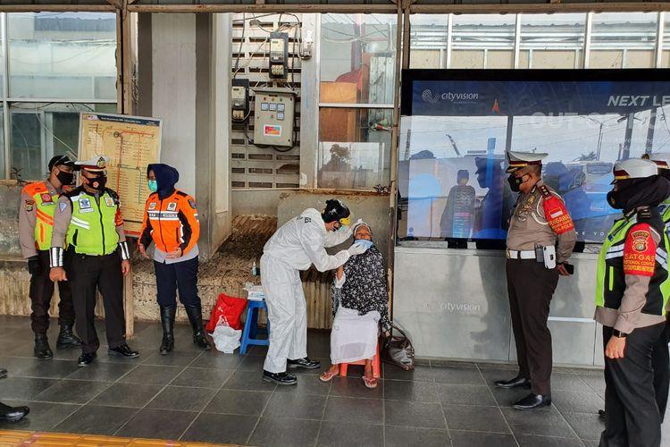 Pembagian masker yang dilakukan Polres Metro Depok kepada salah satu pengguna kereta di Stasiun Depok Baru, Kota Depok, Jawa Barat, Jumat (12/2/2021) siang.