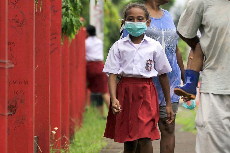 Seorang siswa SD dengan masker di wajahnya berjalan meninggalkan sekolah usai melakukan pendaftaran ulang pada hari pertama sekolah di Jayapura, Papua, Senin (13/7/2020). Siswa SD, SMP dan SMA mulai mengikuti kegiatan belajar-mengajar tahun ajaran baru 2020/2021 dengan sistem pembelajaran tatap muka langsung dan daring.