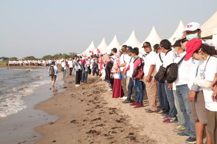 Para peserta Menghadap ke Laut menggelar aksi di timur Ancol, Jakarta Utara, Minggu (19/8/2018).