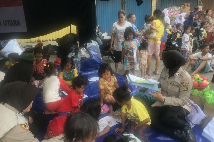 Sejumlah Polisi Wanita (Polwan) menghibur anak-anak korban pengungsian di Kampung Bandan, Ancol, Padamangan, Jakarta Utara Selasa (14/5/2019).
