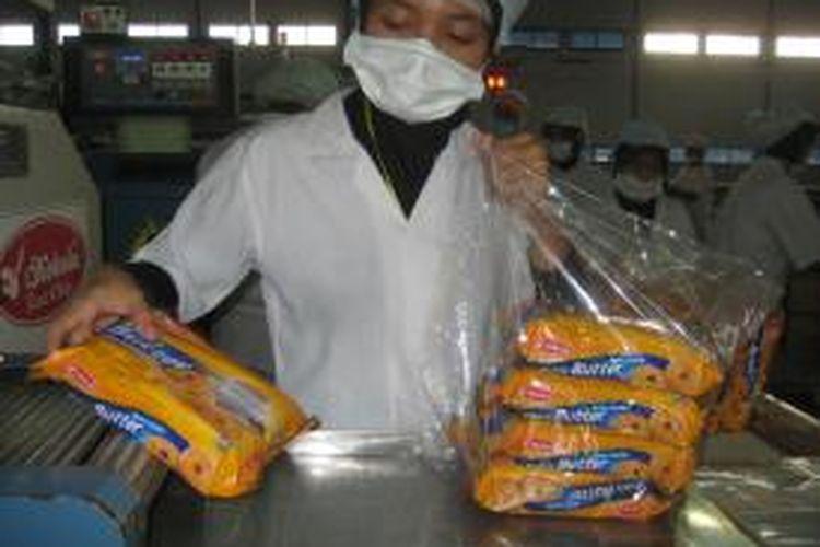 Ilustrasi: Pekerja mengepak produk biskuit Kokola di bagian akhir mesin produksi.