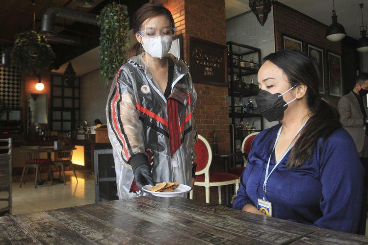 Pelayan di restoran Arista Palembang menggunakan jas hujan sebagai salah satu upaya mengikuti protokol kesehatan, Jumat (18/12/2020).