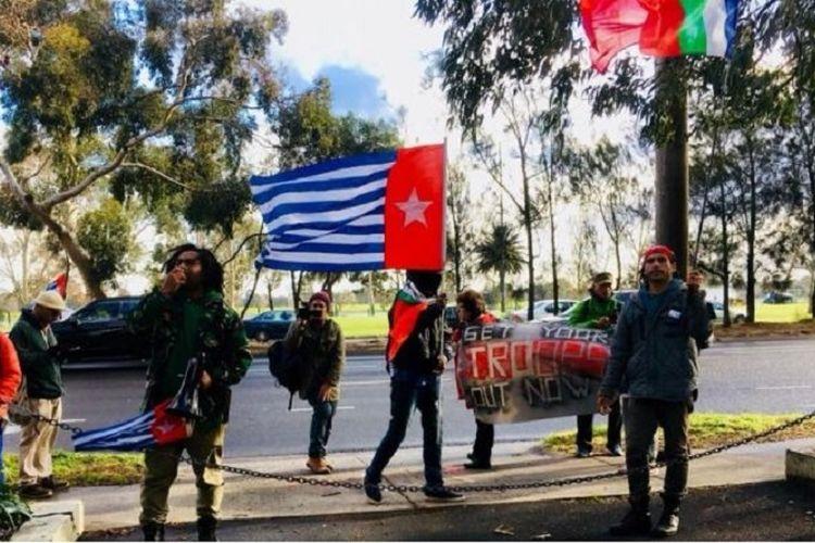 Pengunjuk rasa mengibarkan bendera kelompok Papua Barat Merdeka di depan kantor KJRI Melbourne.