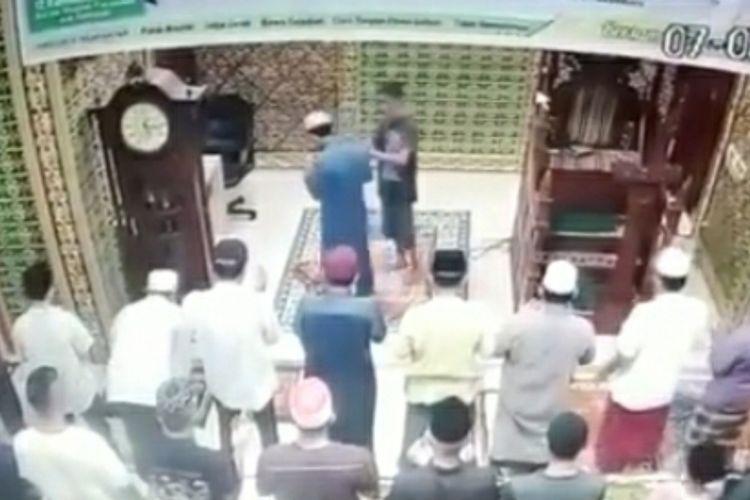 Tangkapan layar rekaman CCTV detik-detik imam masjid ditampar seorang pria berbaju kaos hitam di Masjid Baitul Arsyi di Jalan Srikandi, Kelurahan Delima, Kecamatan Bina Widya, Kota Pekanbaru, Riau, Jumat (7/5/2021).