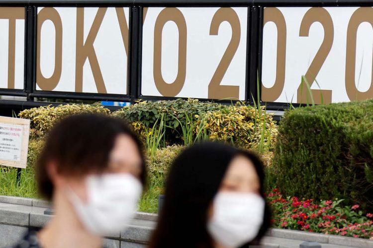 Orang-orang memakai masker pada 27 Juni 2021 berjalan melewati spanduk iklan Olimpiade Tokyo 2020, yang telah ditunda hingga 2021 karena pandemi Covid-19 di Tokyo, Jepang.