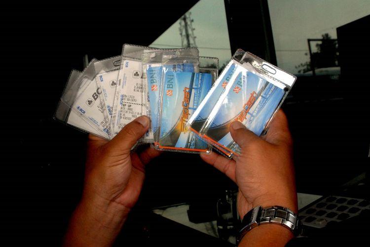 Petugas memperlihatkan kartu uang elektronik yang dibagikan secara cuma-cuma di gerbang pintu tol Jagorawi Citeureup, Kabupaten Bogor, Jawa Barat, Senin (16/10/2017). Sebanyak 1,5 juta uang elektronik akan dibagikan gratis mulai 16 Oktober hingga 31 Oktober 2017. Masyarakat cukup membayar saldonya saja. Pembebasan biaya kartu ini bertujuan untuk meningkatkan penetrasi pembayaran nontunai di gerbang tol sampai 100 persen. ANTARA FOTO/Yulius Satria Wijaya/kye/17.
