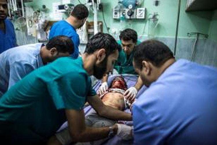 Seorang dokter di RS Kamal Adwan, Beit Lahia, Jalur Gaza tengah sibuk menangani seorang anak perempuan yang terluka akibat serangan Israel pada 22 Juli lalu.