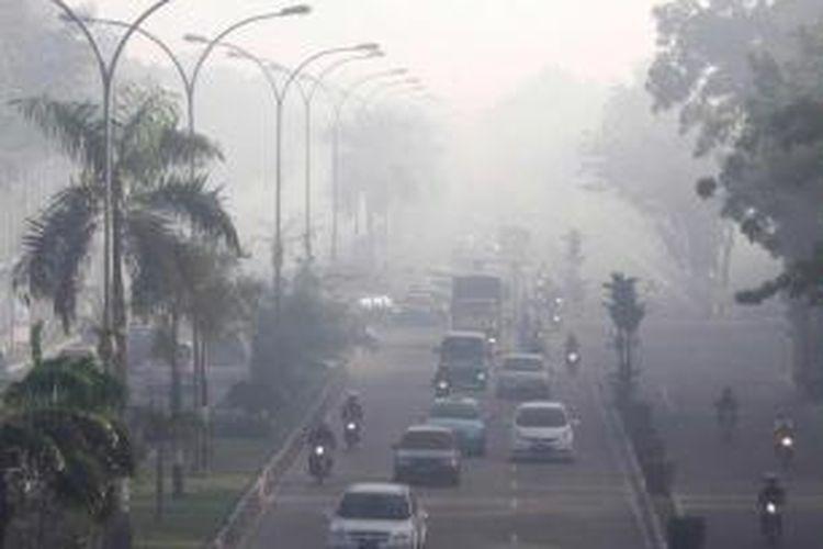 Pengendara tetap melakukan aktivitas luar ruangan meski kabut asap pekat menyelimuti kota Pekanbaru dengan jarak pandang kurang dari 750 meter, Kamis (20/6/2013). Berdasarkan pantauan data satelit NOAA18 di Kementerian Kehutanan, jumlah hotspot di Riau mencapai 148 titik.