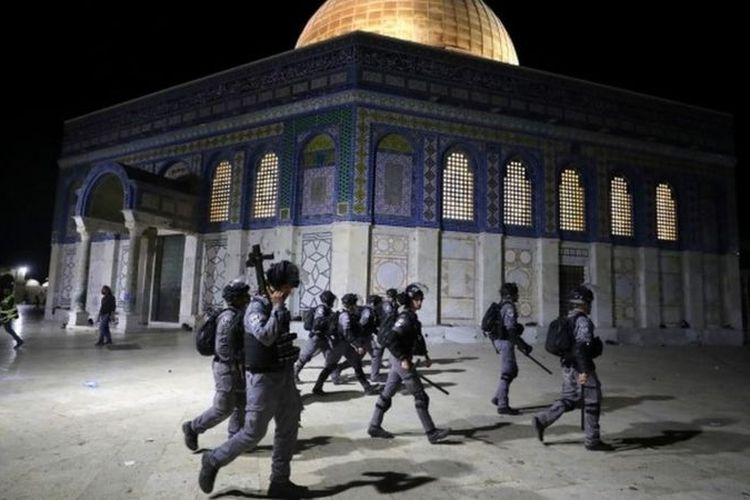 Polisi Israel berjalan melewai tempat suci Dome of the Rock saat bentrokan dengan warga Palestina.