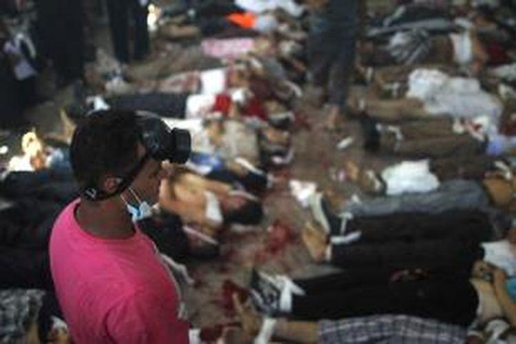 Seorang pria berdiri di depan deretan jenazah para korban kerusuhan di Mesir, Rabu (14/8/2013). Lebih dari 120 orang dilaporkan telah tewas, setelah pasukan keamanan menyerbu perkemahan para demonstran pendukung Presiden terguling Mesir Muhammad Mursi.