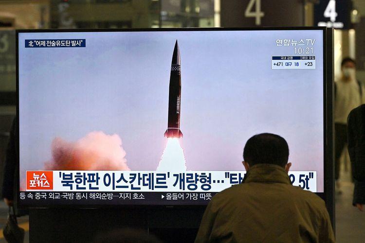 Seorang pria menyaksikan dari layar televisi di stasiun kereta Suseo, Seoul, pada 26 Maret, berisi tayangan uji coba rudal balistik terbaru Korea Utara.