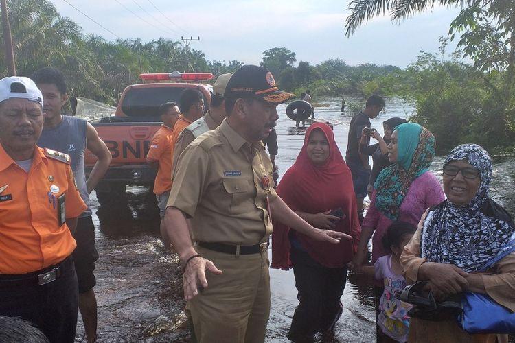 Kepala BPBD Riau, Edward Sanger (baju dinas cokelat) menemui sejumlah warga untuk menyampaikan agar mengawasi anak-anak yang mandi di lokasi banjir di Desa Buluh Cina, Kecamatan Siak Hulu, Kabupaten Kampar, Riau, Senin (23/12/2019).