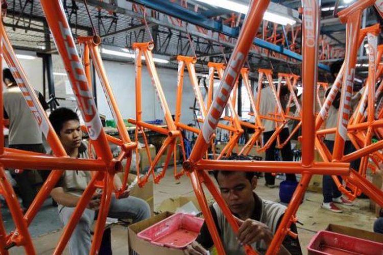 Pekerja memasang label di kerangka sepeda merek SCOTT di pabrik sepeda PT Insera Sena di Desa Wadungasih, Bunduran, Sidoarjo, Jawa Timur, beberapa waktu lalu.