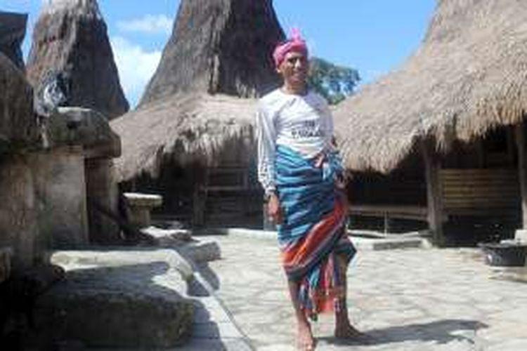 Rato (raja-imam) Lado Regi Tera sebagai Rato Tarung mengenakan kain tenun tradisional, berdiri di samping rumah adatnya di  kampung adat Tarung, Waikabubak.