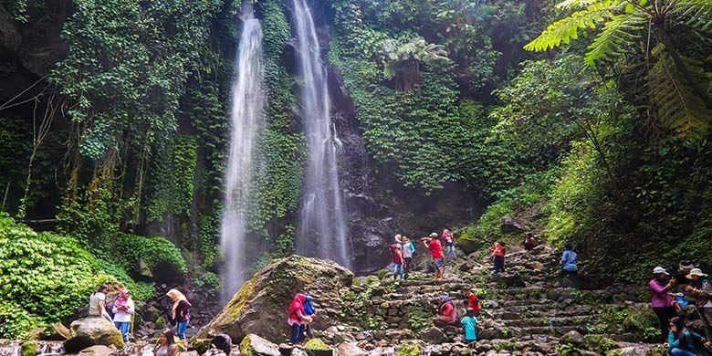 Wisatawan sedang menikmati suasana di bawah aliran Air Terjun Jumog