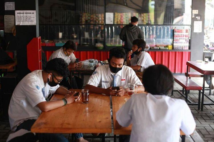Pelajar memanfaatkan internet gratis di Warkop Pitulikur, Surabaya.