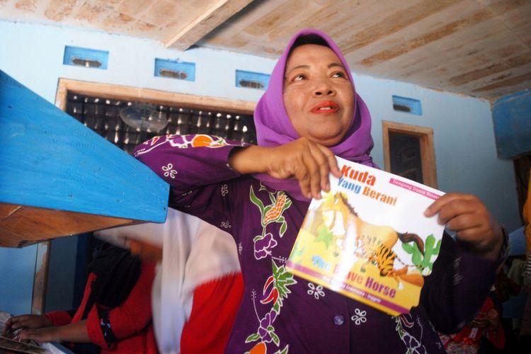 Inayati (50), warga Desa Ngombak, Kecamatan Kedungjati, Kabupaten Grobogan saat mendongeng di Taman Baca Luru Ilmu di Dusun Kedokan, Desa Ngombak, Senin (30/7/2018) sore.