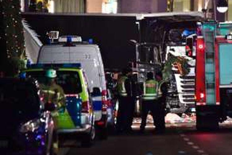 Sejumlah aparat kepolisian tengan memeriksa truk yang dipakai untuk menabrak sebuah pasar malam yang menjual keperluan Natal di pusat Kota Berlin, Senin (18/12/2016).
