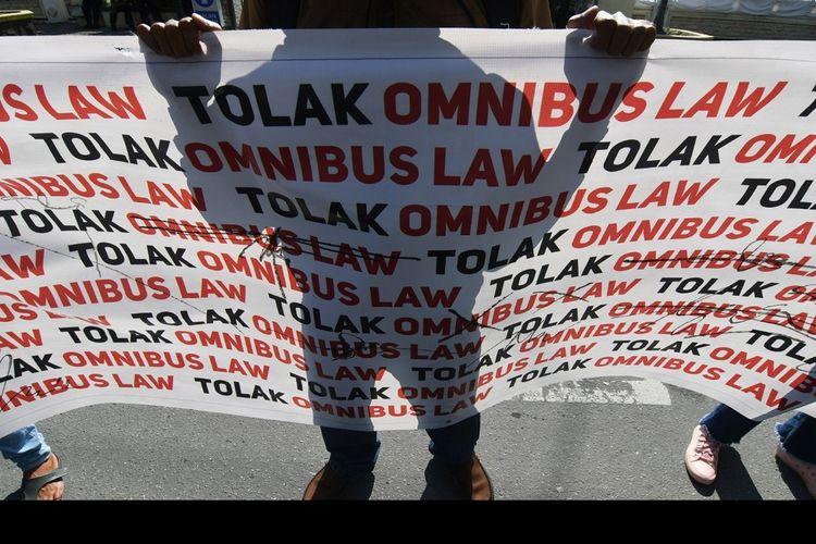 Pengunjuk rasa yang tergabung dalam Front Rakyat Tolak Omnibus Law (Frontal) membawa spanduk saat melakukan aksi unjuk rasa di Depan Gedung DPRD Sulawesi Tengah di Palu, Sulawesi Tengah, Jumat (14/8/2020). Mereka menyatakan menolak rencana pengesahan RUU Omnibus Law Cipta Kerja. ANTARA FOTO/Mohamad Hamzah/nz.