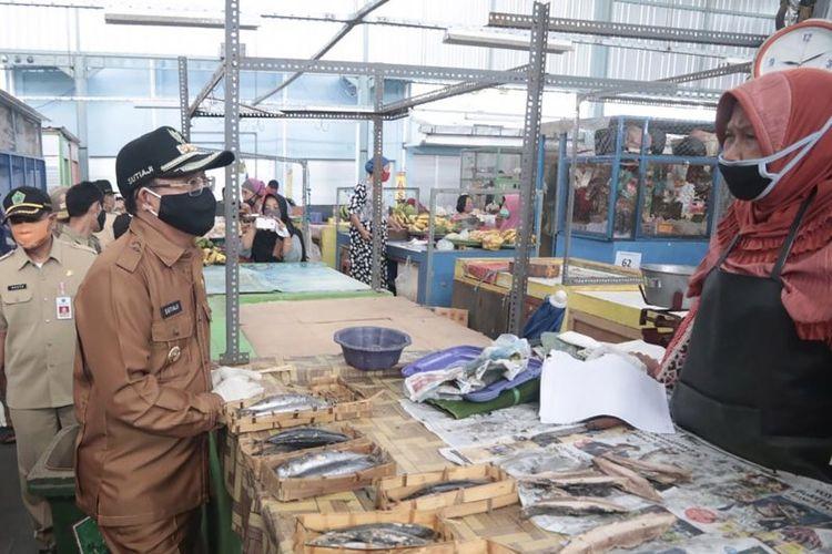 Wali Kota Malang Sutiaji (kiri) berbicara dengan salah seorang pedagang saat memantau penerapan pola ganjil genap di Pasar Bunul, Kecamatan Blimbing, Kota Malang, Jawa Timur, Senin (18/5/2020).