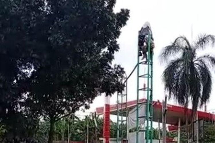 Seorang pria nekat memanjat tiang papan reklame di Jalan Bintaro Sektor 3, Pondok Aren, Tangerang Selatan, Jumat (13/3/2021).