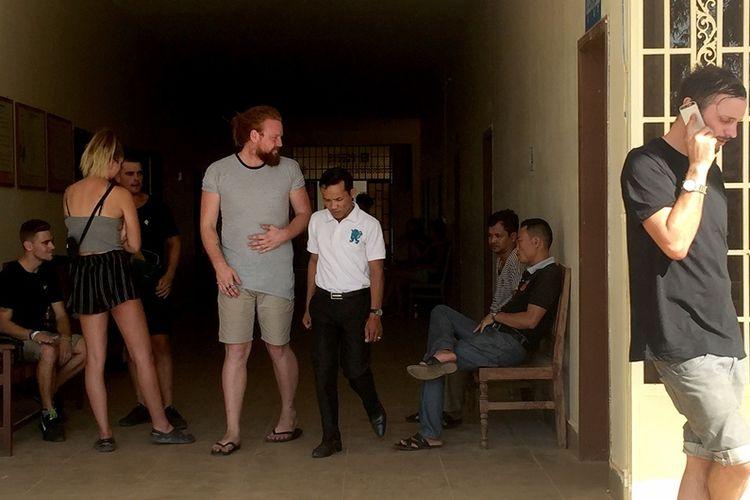 Beberapa orang asing berada di luar ruang sidang di provinsi Siem Reap, Kamboja. Mereka ditangkap pada Kamis (25/1/2018) karena diduga bernyanyi dan menari secara pornografi. (AFP/Chan Raksmey)