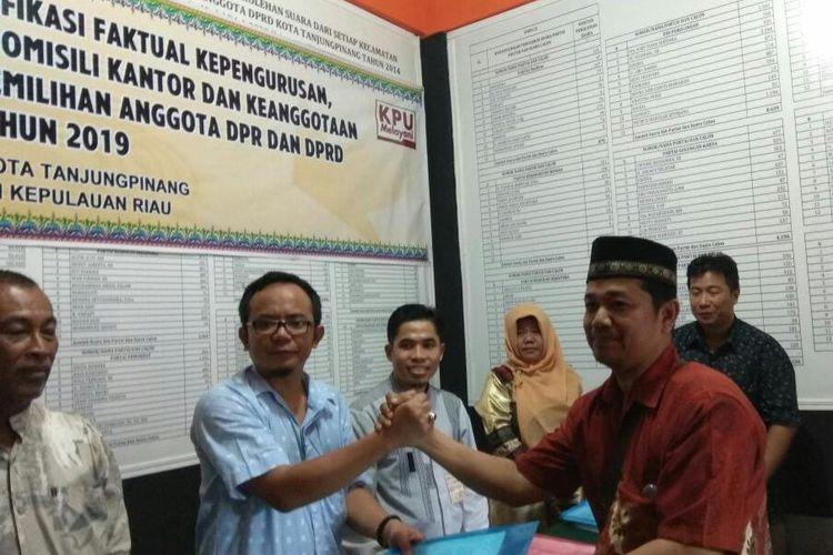 Komisioner KPU menyerahkan hasil verifikasi kepada salah satu pengurus partai dari 12 partai politik yang diverifikasi.