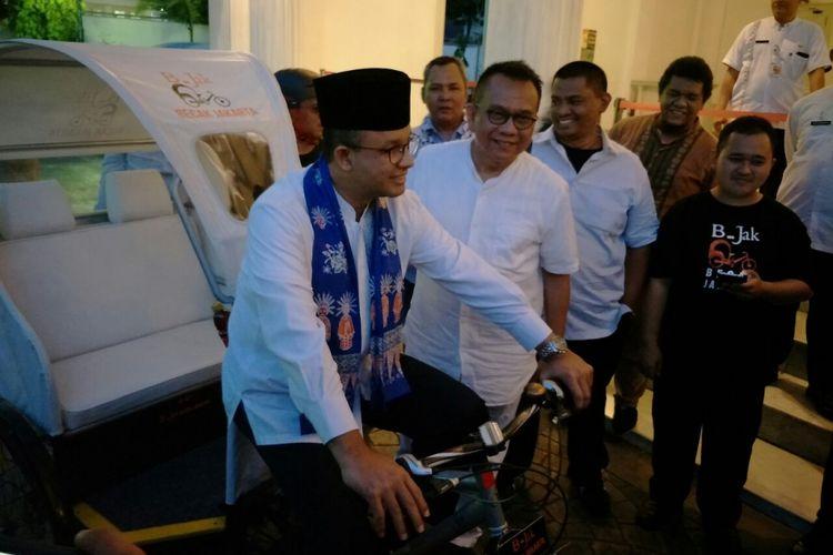 Gubernur DKI Jakarta Anies Baswedan mencoba becak modifikasi yang ditunjukan Wakil Ketua DPRD DKI Jakarta Mohamad Taufik di Balai Kota, Jumat (11/5/2018).