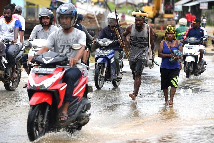 Warga dengan peralatan berburu melintasi genangan air pasca banjir bandang melanda wilayah Sentani, Jaya Pura, Papua, Senin (18/3/2019). Akibat banjir bandang yang melanda Sentani sejak Sabtu (16/3) lalu, sedikitnya empat ribu warga mengungsi di sejumlah posko pengungsian. ANTARA FOTO/Zabur Karuru/foc.