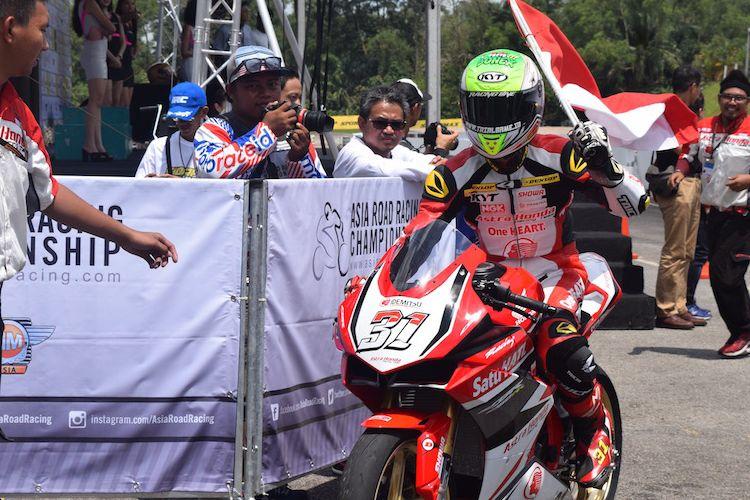 Pebalap Astra Honda Racing Team, Gerry Salim, memasuki parc ferme dengan membawa bendera Marah Putih setelah memenangi balapan kedua Asia Production 250cc seri pertama Asia Road Racing Championship di Sirkuit Johor, Malaysia, Minggu (2/4/2017).