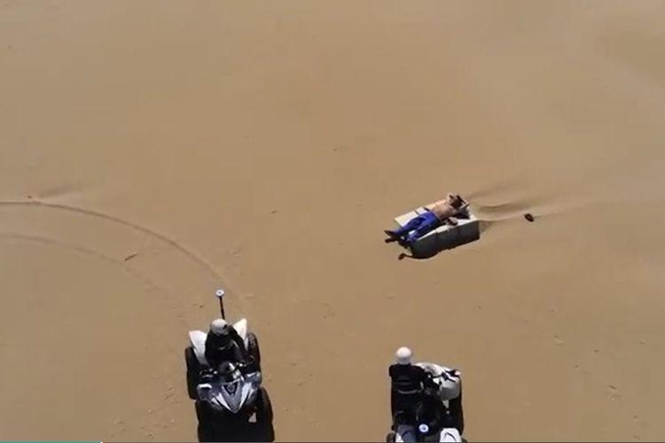 Potongan video memperlihatkan dua polisi di Rimini, Italia, mendekati seorang pria yang tengah berjemur di pantai. Ribuan orang dihukum pada akhir pekan karena melanggar aturan lockdown virus corona.