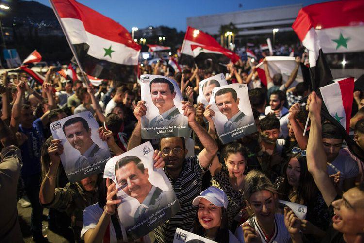 Pendukung Presiden Suriah Bashar Assad mengangkat bendera nasional dan gambar Assad saat mereka merayakannya di Omayyad Square, di Damaskus, Suriah, Kamis, 27 Mei 2021.