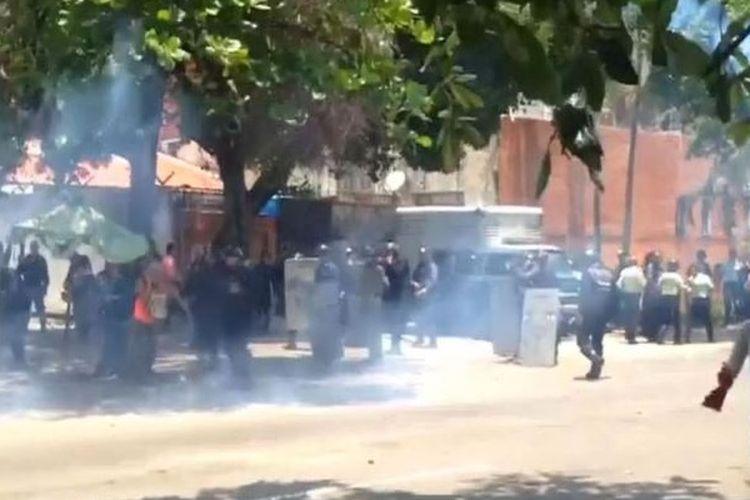 Keluarga dari tahanan di Penjara Valencia, Venezuela berhamburan setelah polisi menembakkan gas air mata Rabu (28/3/2018).  Terjadi kerusuhan di sana setelah sekelompok tahanan berusaha melarikan diri dengan meledakkan kasur.
