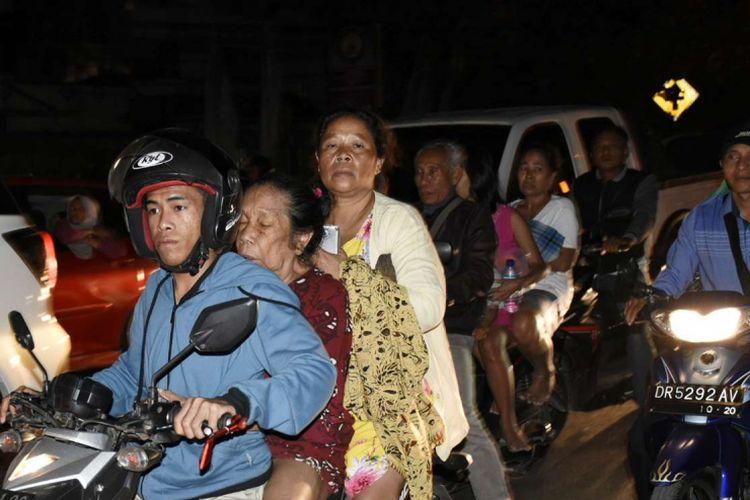 Warga yang panik menaiki sepeda motor ketika terjadi gempa bermagnitudo 7 di Kecamatan Ampenan, Mataram, NTB, Minggu (5/8/2018).
