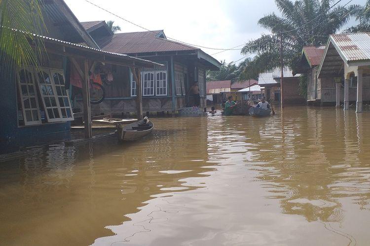 Ketinggian banjir yang terus bertambah di permukiman warga Desa Buluh Cina, Kecamatan Siak Hulu, Kabupaten Kampar, Riau, Selasa (24/12/2019). Sejumlah warga beraktivitas menggunakan perahu.