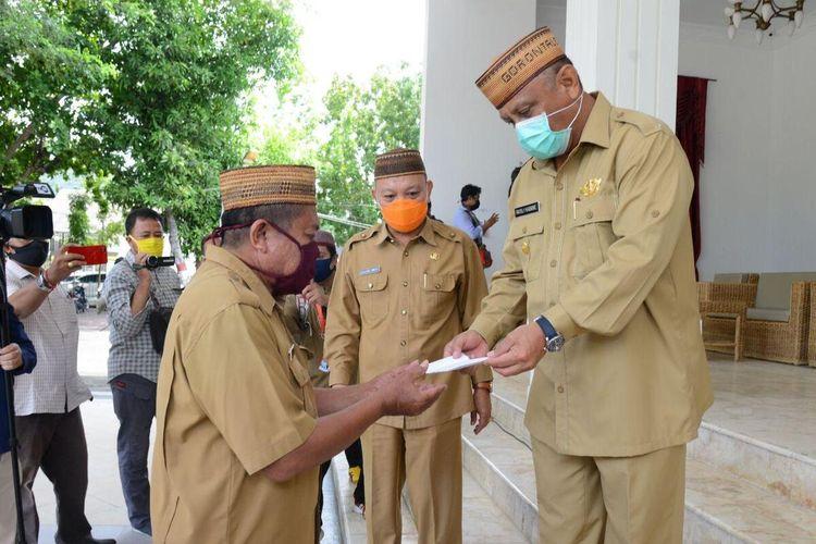 Gubernur Gorontalo Rusli Habibie saat menyerahkan secara simbolis THR pada perwakilan PNS di pemerintahan Provinsi Gorontalo. Semua gaji dan tunjangan PNS selama ini dibayarkan langsung ke rekening istri pegawai.