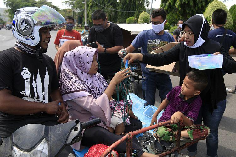 Damma Yanti sedang menyerahkan masker dan hand sanitizer kepada tukang becak di kawasan Kota Banda Aceh, Minggu (05/04/2020)