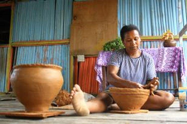 Penduduk Desa Abar tengah membuat gerabah di teras rumahnya di Pulau Abar, Danau Sentani, Jayapura, Papua.